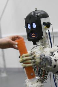 BERT2، إنسالي (روبوت) مساعِد بشري الشكل، يقدم شيئًا إلى إنسان حقيقي. حقوق الطبع: مختبر الإنساليات (الروبوتيات Robotics) لجامعة بريستول البريطانية.